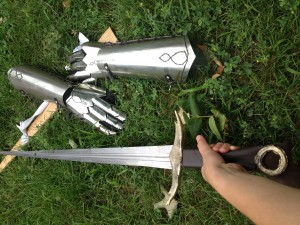 The blade, cross-guard, and pommel in their positions, along with her sheath and gauntlets (made with friend at Madison East metal shop) in the background