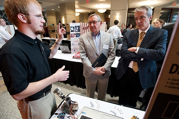 Chris Meyer, a graduate student in mechanical engineering, describes Sector67, his company proposal for a nonprofit, membership-based center to nurture electronics and mechanical prototyping and advanced manufacturing in Madison, to judges Dick Wilkey, center, founder of the Fisher-Barton Group, and John Neis, right, partner with Ventures Investors LLC, during the 2010 G. Steven Burrill Business Plan Competition held at Grainger Hall at the University of Wisconsin-Madison on April 23, 2010. Meyer's plan was awarded second place and $7,000. (Photo by Jeff Miller/UW-Madison)